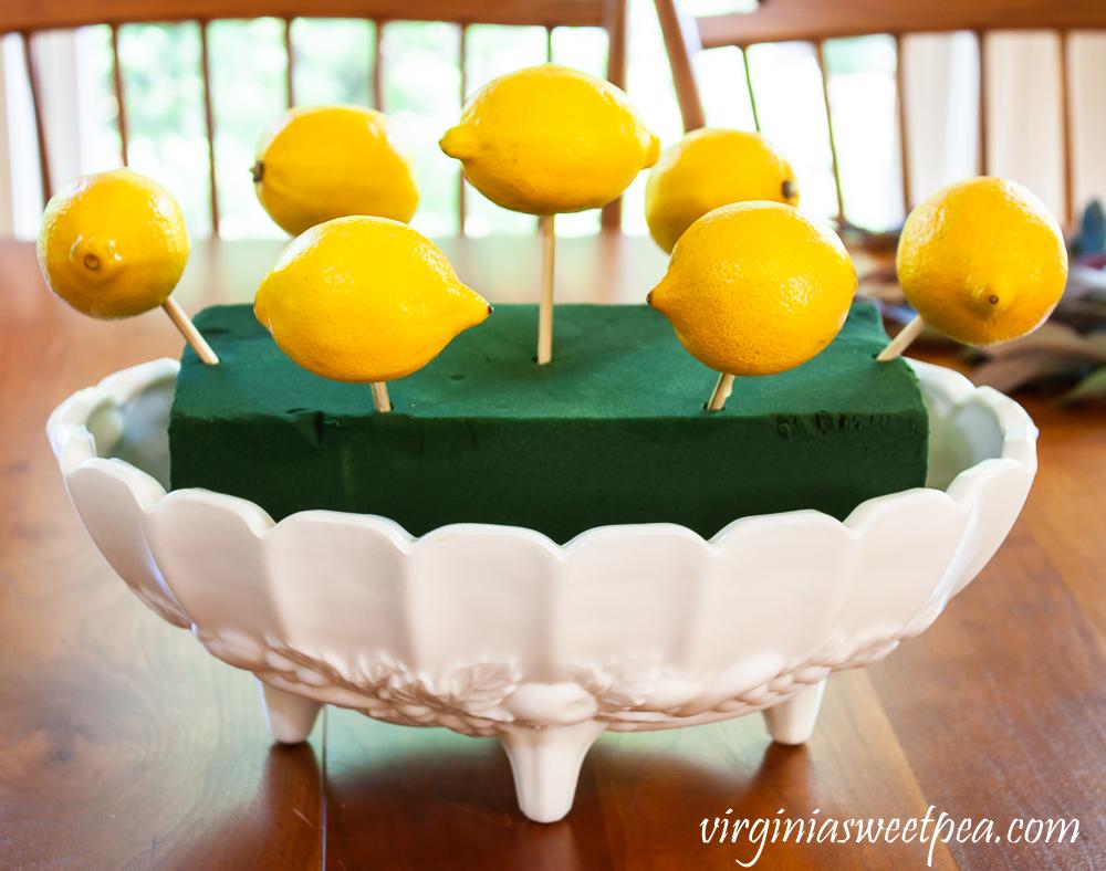 Lemons on skewers arranged in white milk glass Indiana fruit bowl