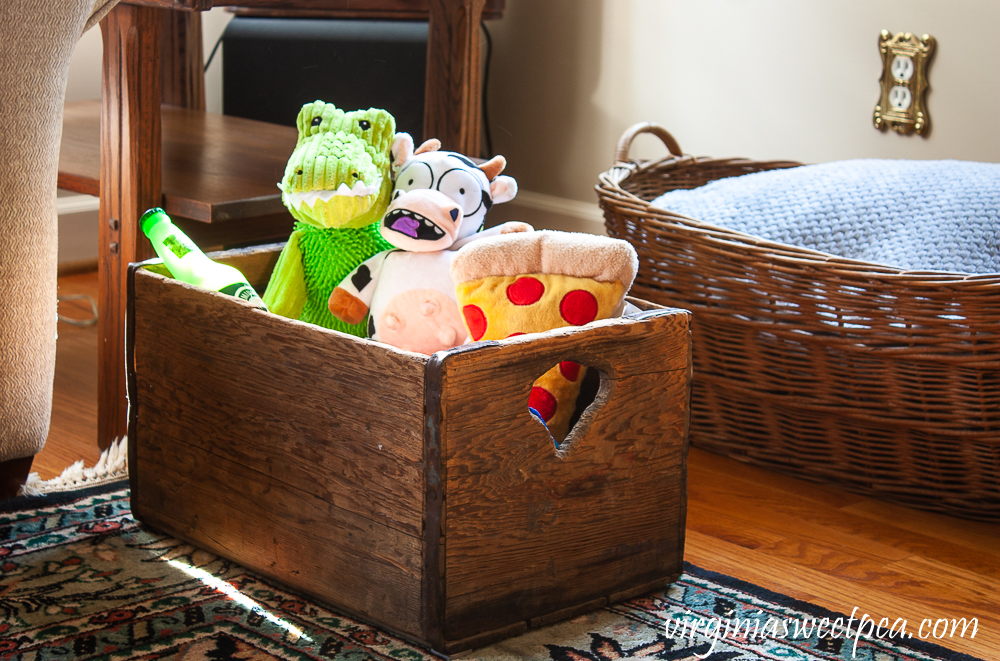 Vintage crate filled with dog toys and a vintage woven laundry basket filled with blankets