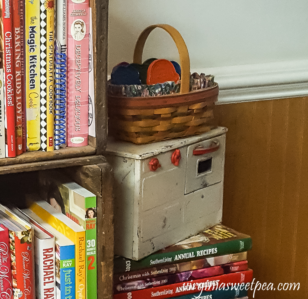 Cookbooks in vintage crates. Antique child stove with a basket filled with vintage cookie cutters.