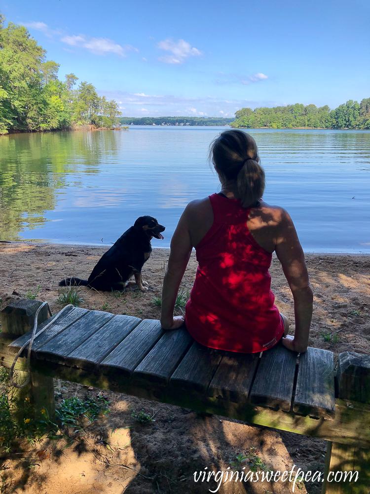 Dog and woman admiring a lake