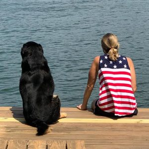 Dog and woman sitting on a dock