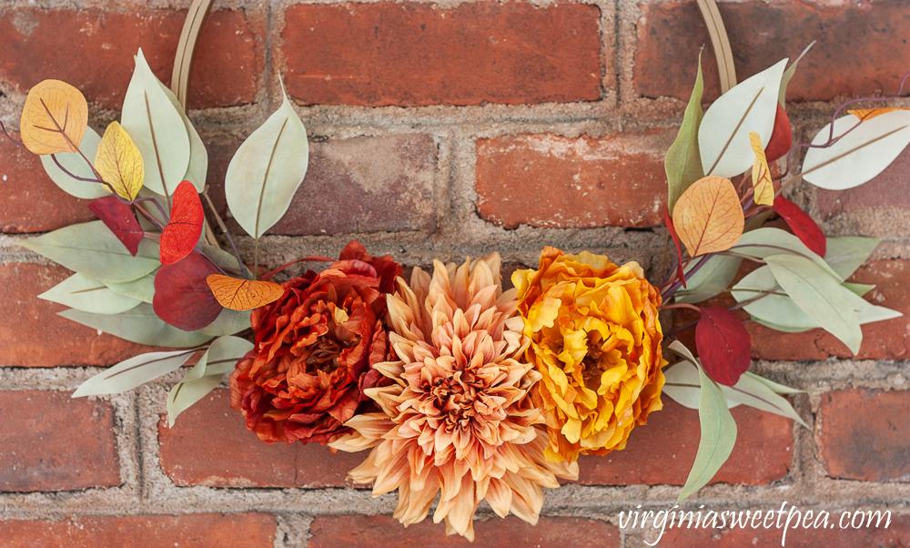 Dark orange, dark blush, and orange faux flowers with greenery on a fall wreath