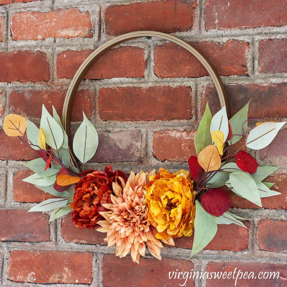 Fall Hoop Wreath hanging on a brick wall