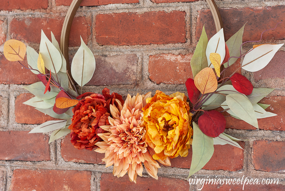 Fall colored peonies and a dahlia with eucalyptus on a fall hoop wreath