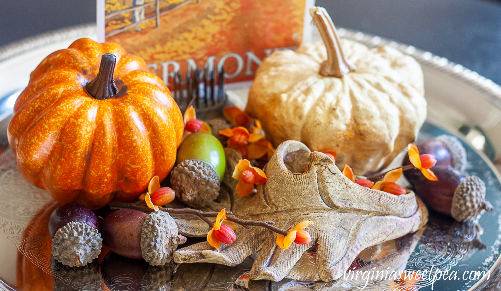 Faux pumpkin, preserved gourd, acorns, bittersweet, pottery leaf and Vermont fall postcard on a silver tray