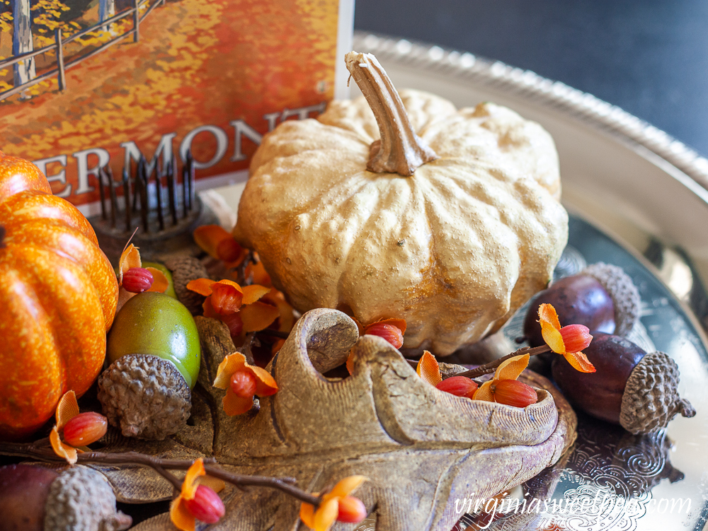 Preserved gourd shaped like a pumpkin on a silver tray with acorns, bittersweet, a pottery leaf, and a Vermont fall postcard