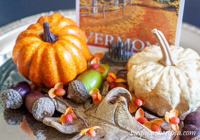 Preserved gourd shaped like a pumpkin on a silver tray with a faux pumpkin, acorns, bittersweet, a pottery leaf, and a Vermont fall postcard