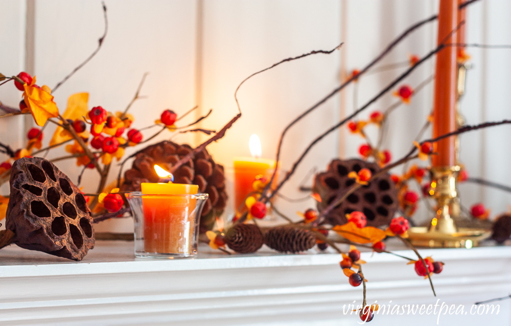 Fall mantel decorated with candles, brass, lotus, pine cones, and bittersweet.