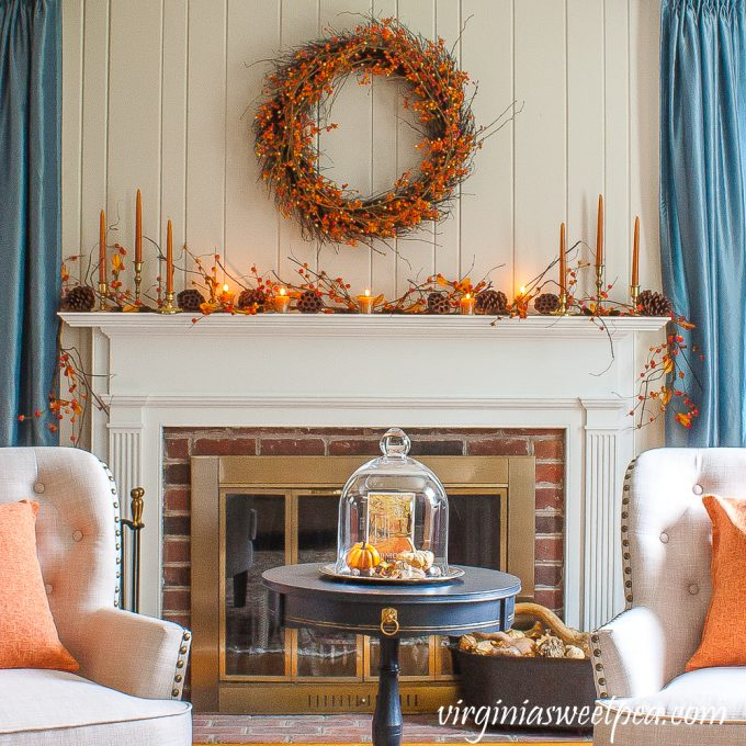 Fall fireplace decorated with items from nature including Bittersweet, Lotus, and Pine Cones.