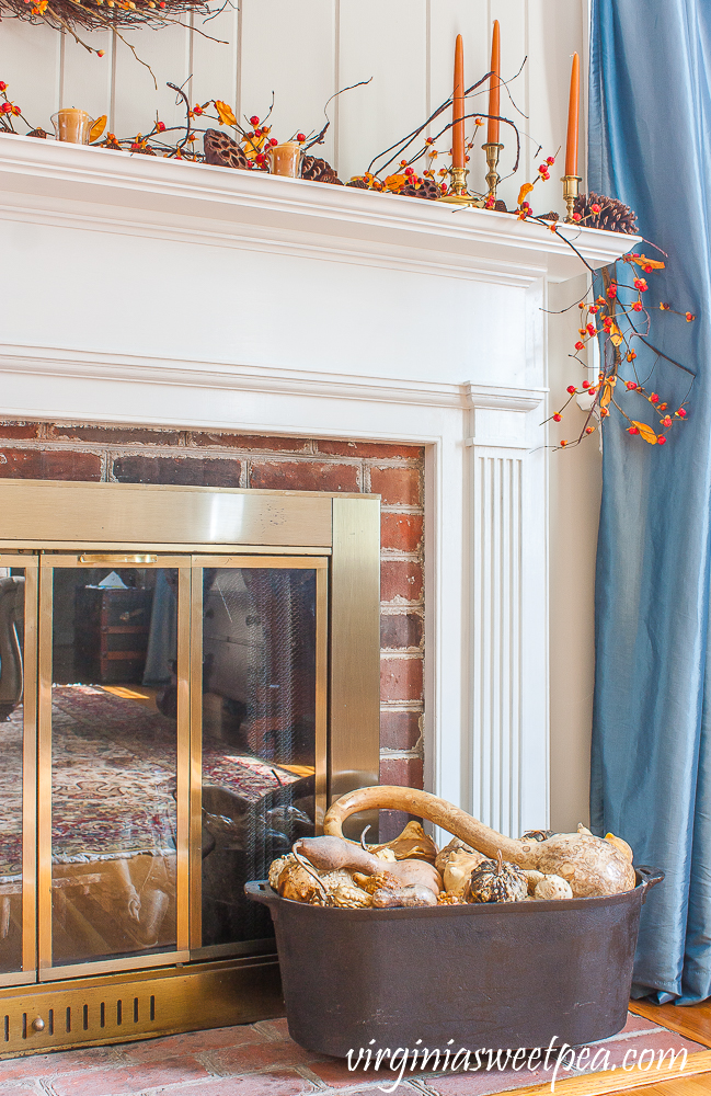 Fall fireplace mantel with dried gourds on the hearth in a black iron tub.