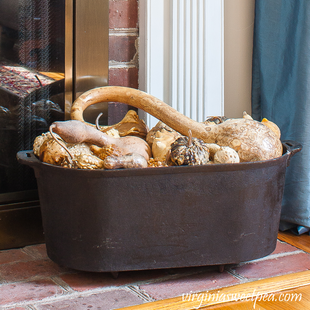 Dried gourds in a black iron tub used on the hearth of a decorated for fall mantel