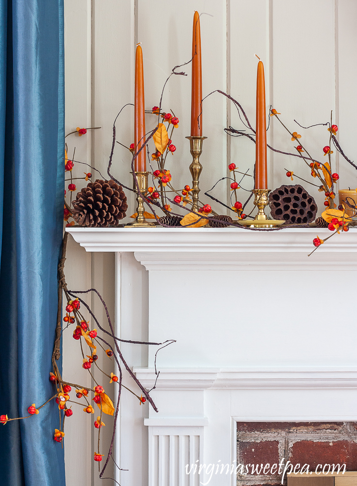Fall mantel decorated with brass candlesticks with orange candles, bittersweet, lotus pods, and pine cones.