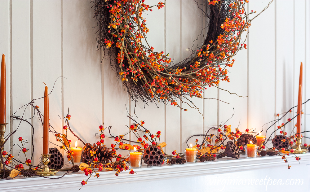 Fall fireplace mantel decorated with bittersweet, lotus pods, pine cones, and candles.