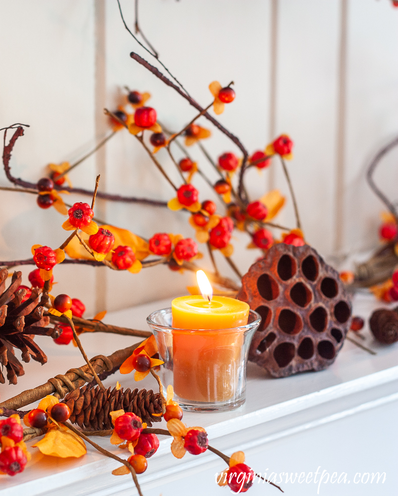 Fall mantel decor with candles, bittersweet, lotus, and pine cones.