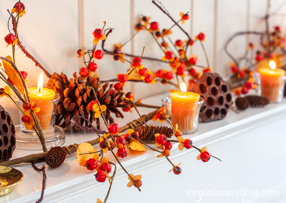 Nature inspired fall mantel decor with bittersweet, pine cones, and lotus pods