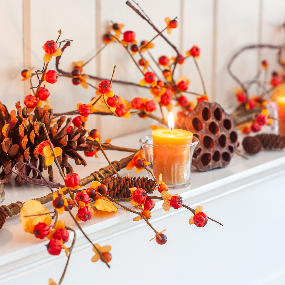 Fall mantel decorated with bittersweet, lotus pods, pine cones, and candles.