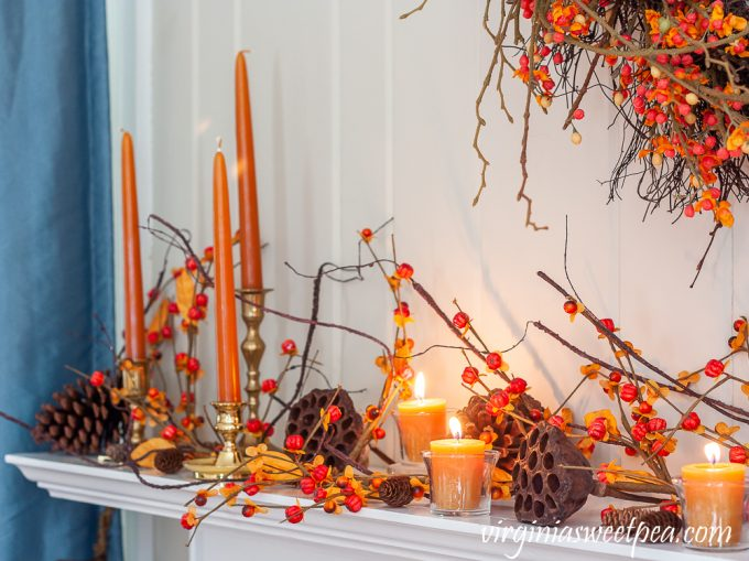 Fall mantel decor with brass candlestick holders, candles, bittersweet, lotus, and pine cones.