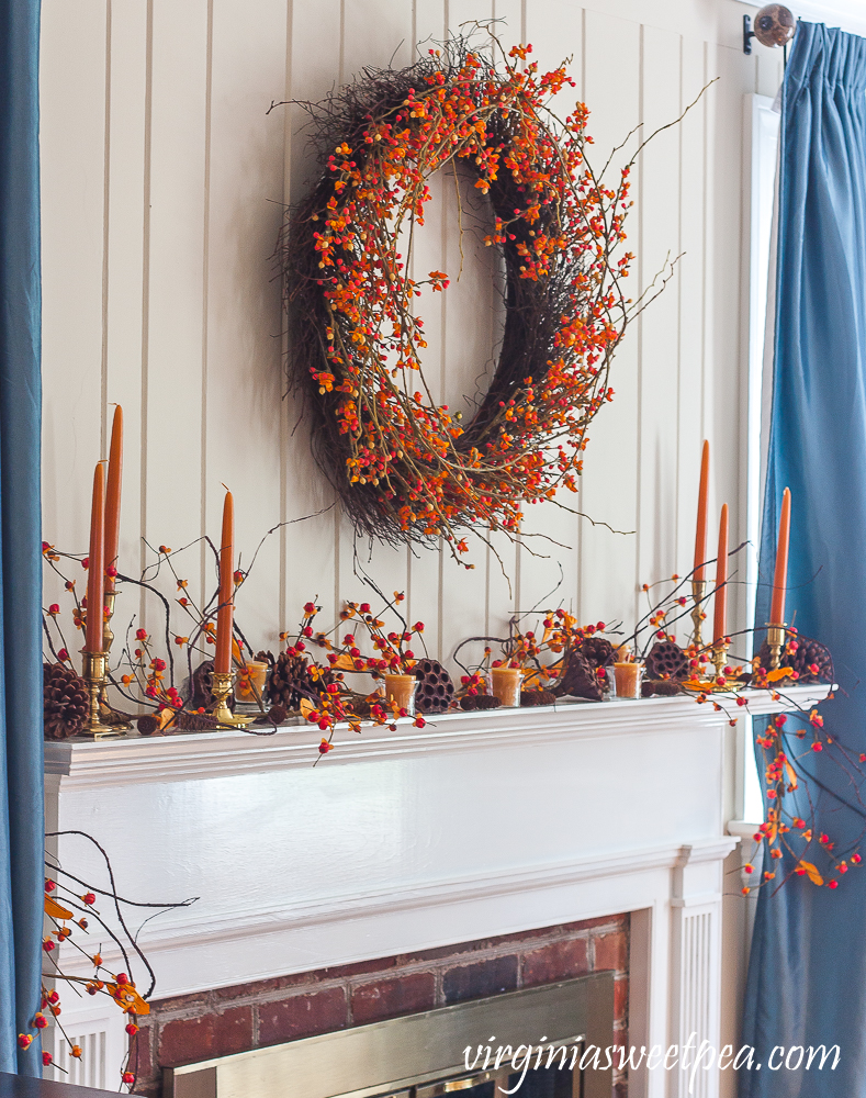 Mantel decorated for fall with bittersweet, lotus pods, pine cones, and candles.