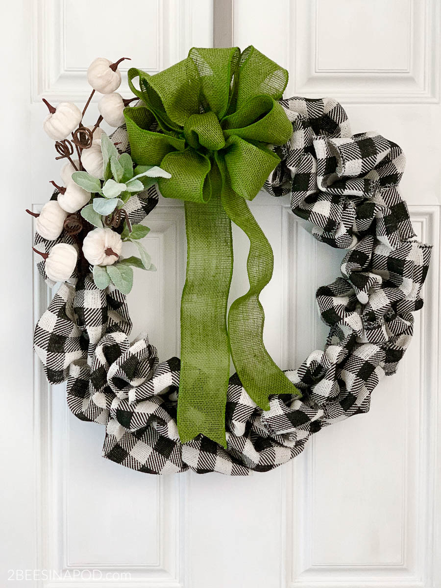 Buffalo check bubble wreath decorated with white pumpkins and a green bow