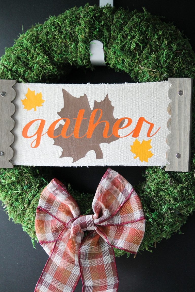 Moss covered fall wreath decorated for fall with a gather sign and a plaid bow