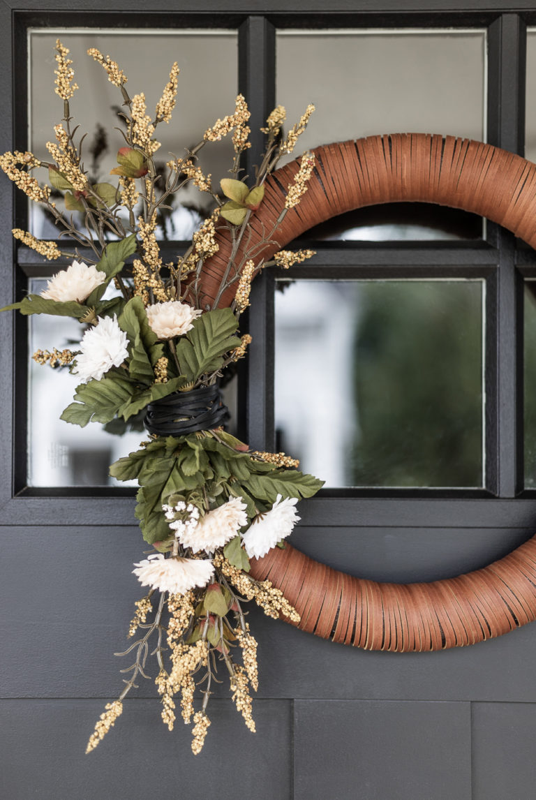 Wreath form wrapped in leather strips decorated for fall with faux florals