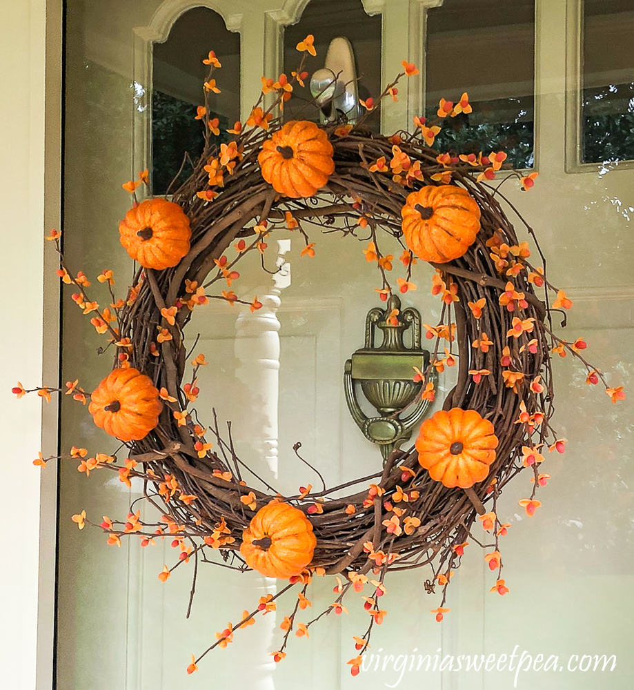 Fall grapevine wreath decorated with pumpkins and bittersweet