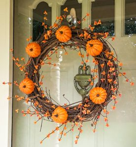 Fall wreath decorated with pumpkins and bittersweet