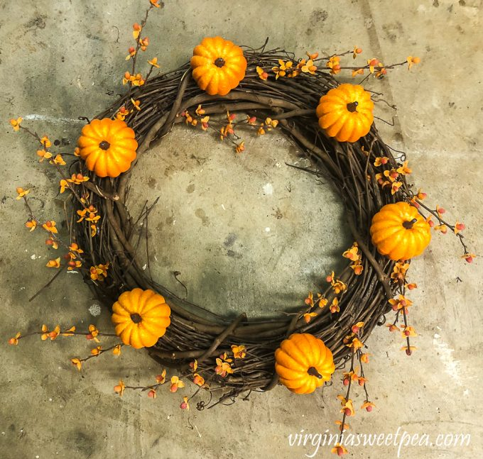 Grapevine wreath with six pumpkins and bittersweet