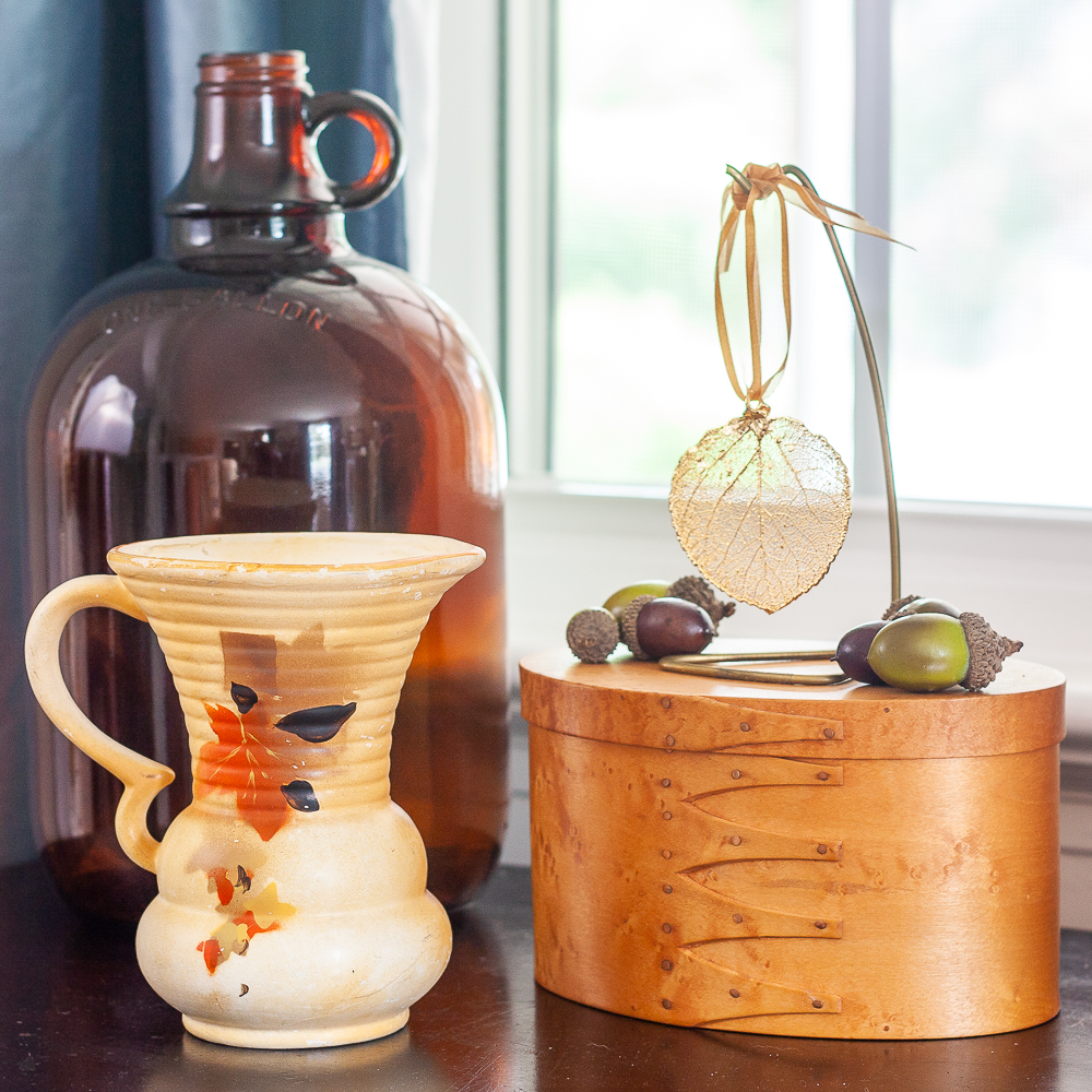Fall Vignette with amber jug, vintage pitcher with leaves on it, wood box topped with a gold dipped leaf and acorns.