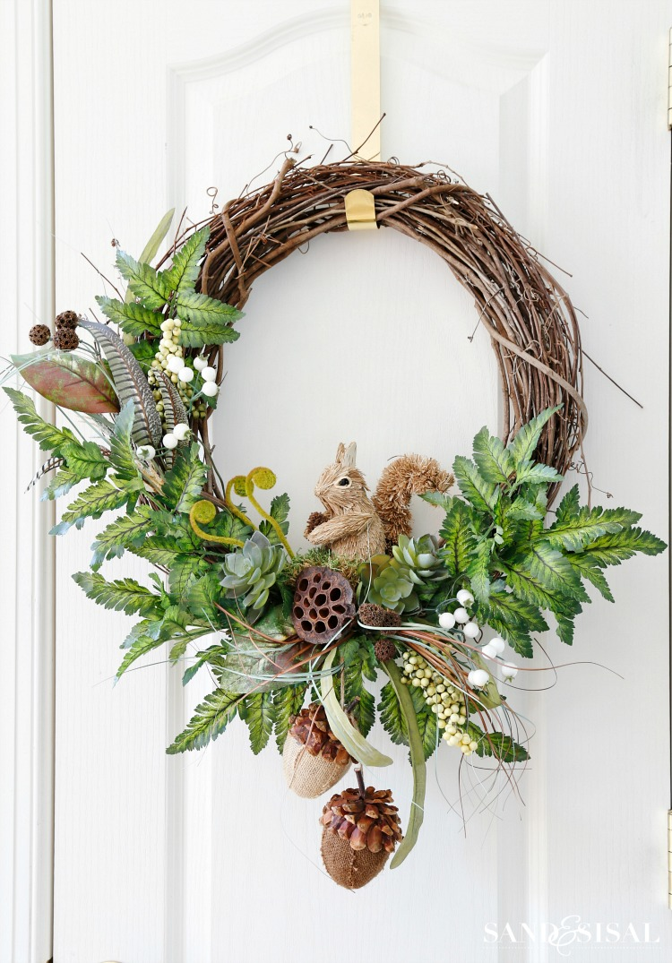 Fall wreath decorated in a woodland style with a squirrel, green foliage, large acorns, and feathers
