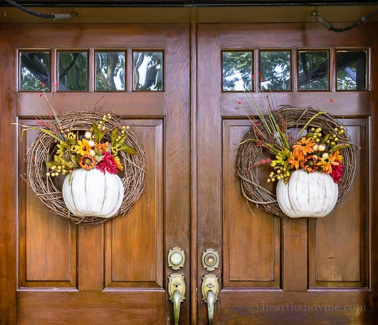 Two fall wreaths with pumpkins and fall florals on double doors.