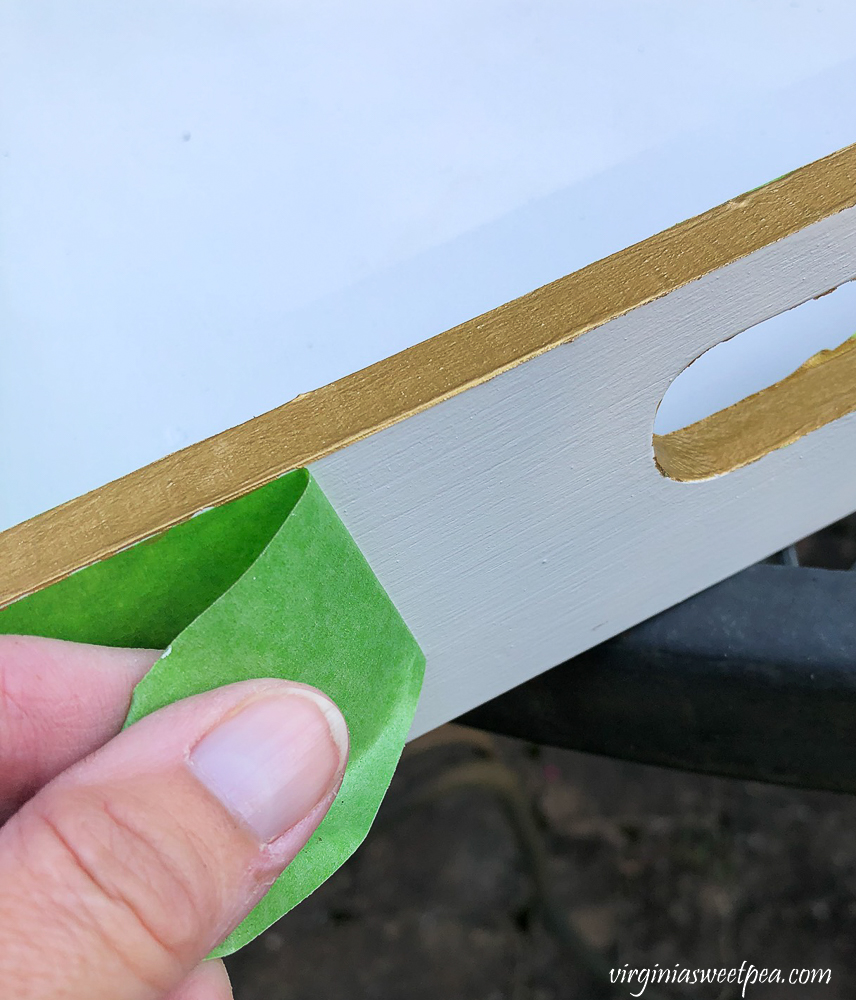 Removing Frog Tape from wooden tray painted white with gold edges