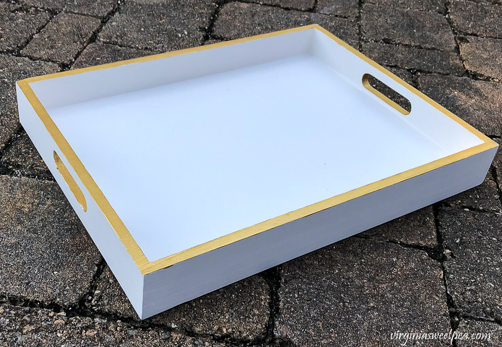 Wooden tray painted white with the edges and handles accented in metallic gold paint.