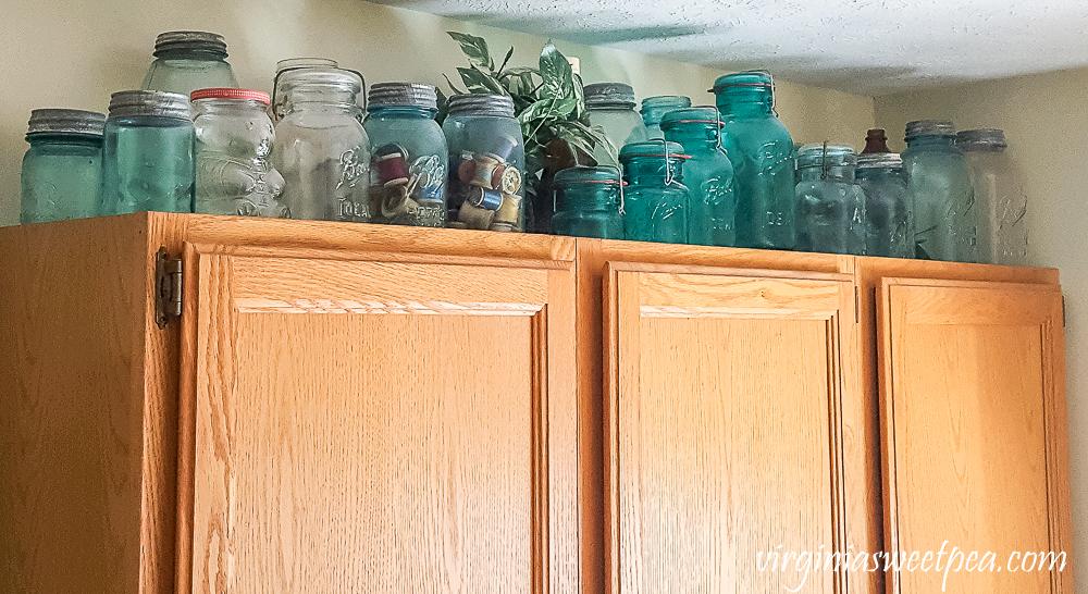 vintage canning jars displayed on top of a cabinet