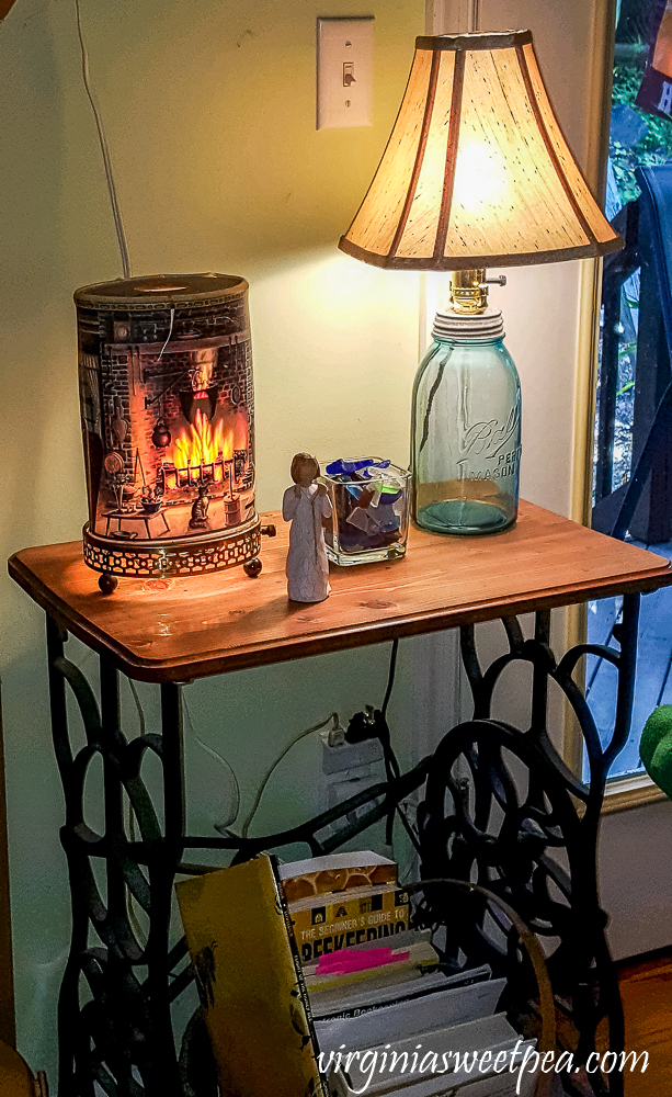 Antique sewing table topped with an Econolite, lamp made from a vintage canning jar, angel, and sea glass.