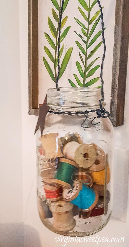 Vintage spools of thread in a Mason jar.