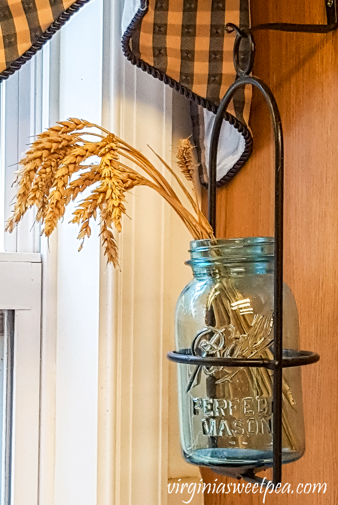 Ball Perfect Mason jar filled with wheat hanging on the side of a cabinet.