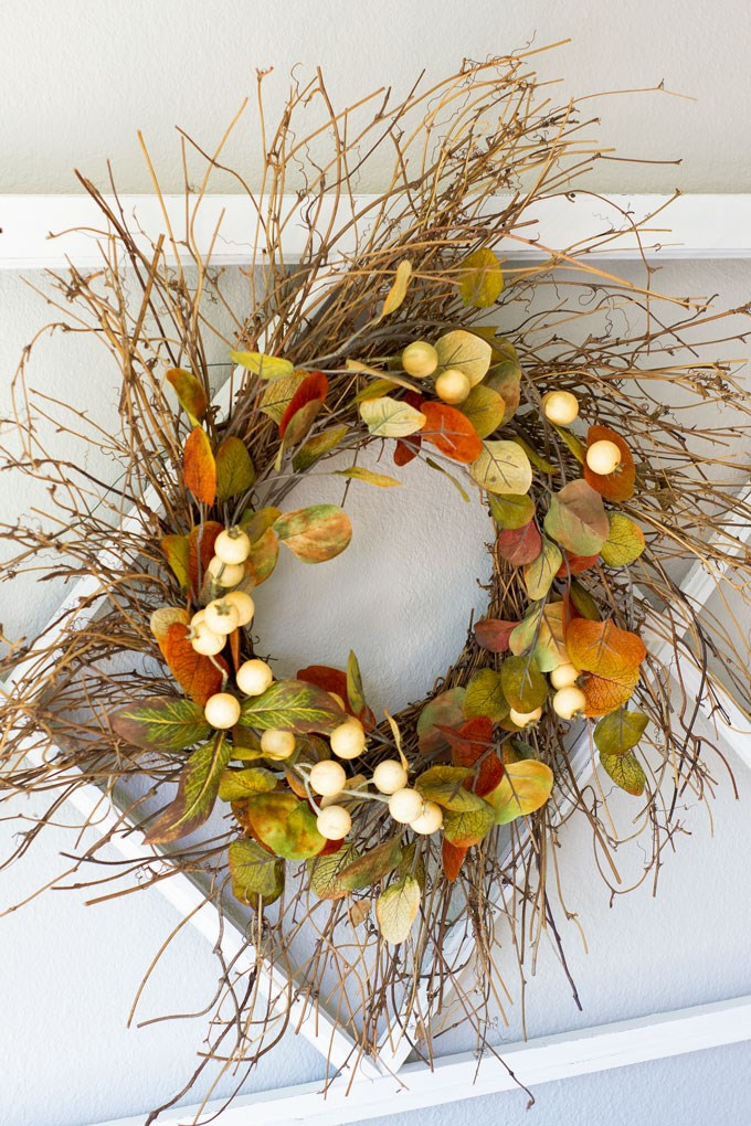 Twiggy fall wreath decorated with faux fall leaves and white berry picks