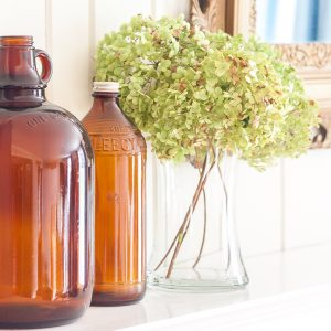 Vintage bottles on a mantel with Hydrangea in a clear glass vase.