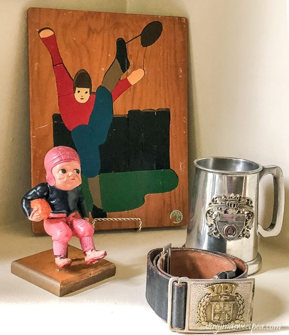 Wood football puzzle from the 1940s and celluloid football player from the 1930s and Virginia Tech corp of cadets belt with belt buckle from the late 50s to early 60s with a Virginia Tech metal mug