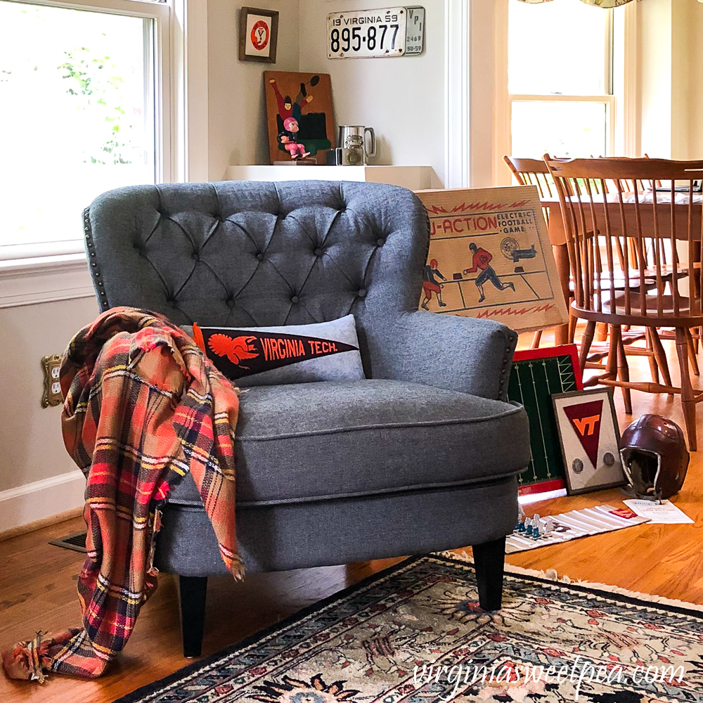 Corner reading nook with gray chair, plaid throw, Virginia Tech pillow, and vintage football collectibles.