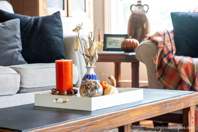 Fall coffee table vignette with a wood tray painted white with gold accents decorated with dried gourds, acorns, mini pumpkins, an orange candle accented with acorns, and a blue chinoiserie vase