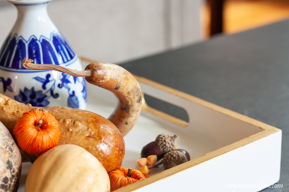 Dried gourds, pumpkins, acorns, and a blue and white chinoiserie vase used to style a tray for fall.