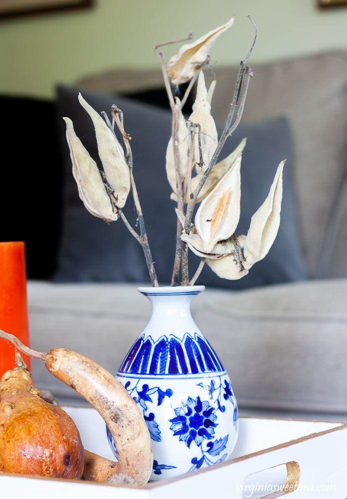 Chinoiserie blue and white vase filled with seed pods on a tray painted white with gold accents.