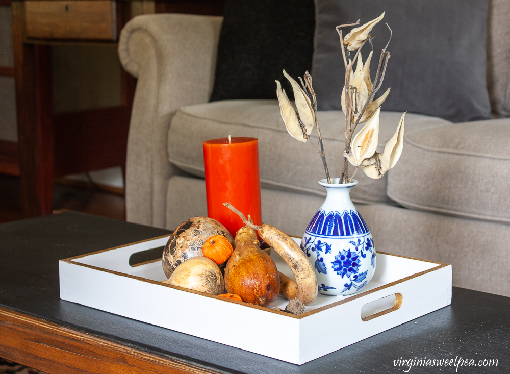 Wood tray painted white and gold styled for fall with dried gourds, acorns, mini pumpkins, an orange candle accented with acorns, and a blue chinoiserie vase