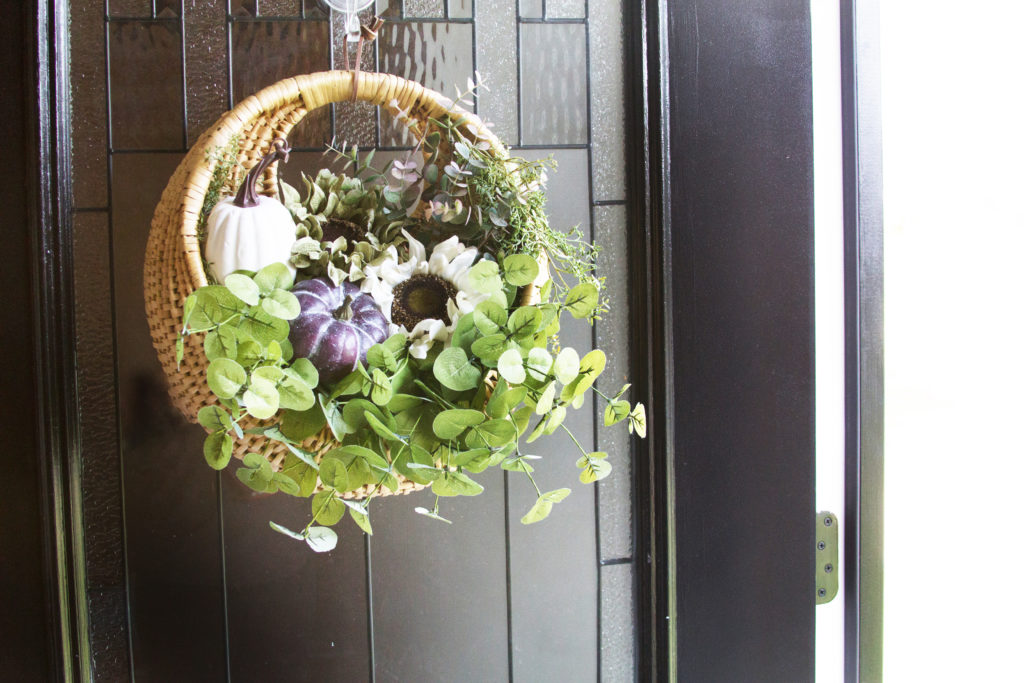 Basket hanging on a front door filled with greenery, a white sunflower, a white pumpkin, and a purple pumpkin