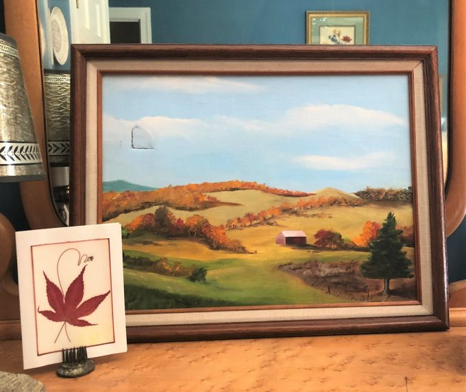 Painting of rolling hills in Vermont in fall and pressed maple leaf