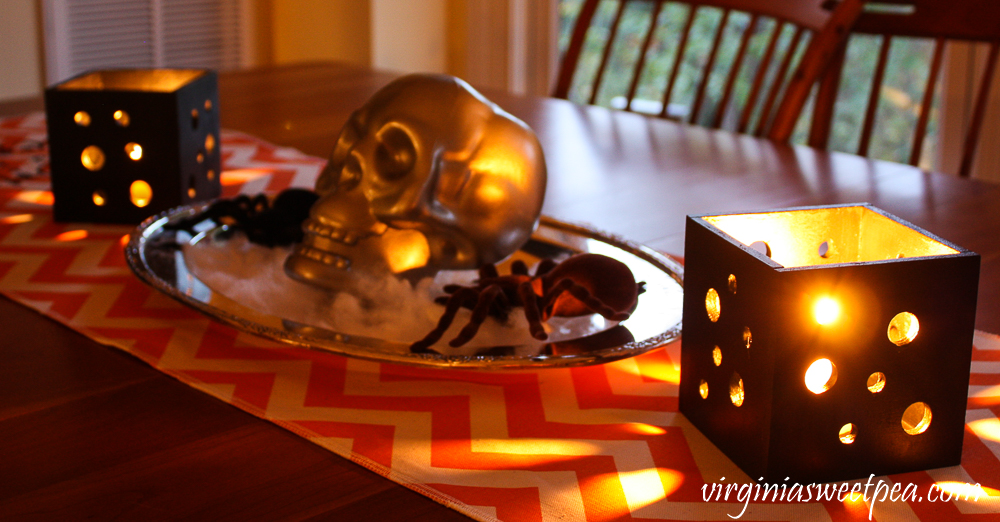 Halloween table decorations with candle holders and skull and spider centerpiece