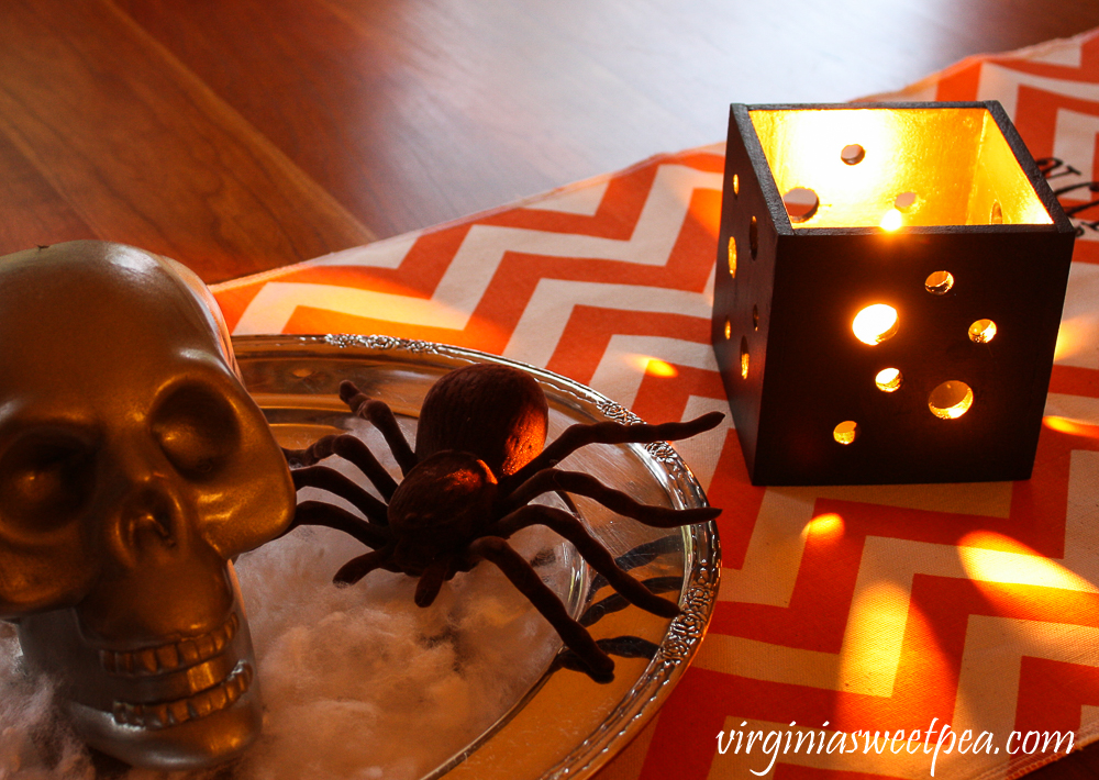 Skull and spider on a silver tray with a orange and white chevron table runner and black square candle holder