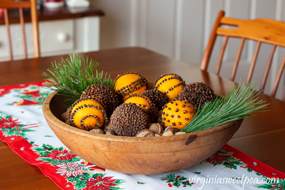 Orange pomanders in a wooden bowl with mixed nuts on the bottom and two sprigs of pine
